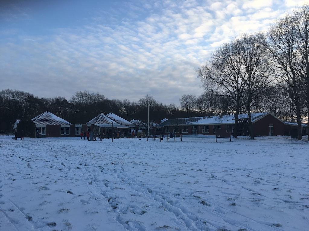 Kinderen spelen buiten in de sneeuw bij school